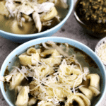 Two blue bowls of pesto chicken tortellini soup topped with parmesan cheese