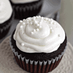 Red velvet cupcake with icing and pearl sprinkles on a small white stand