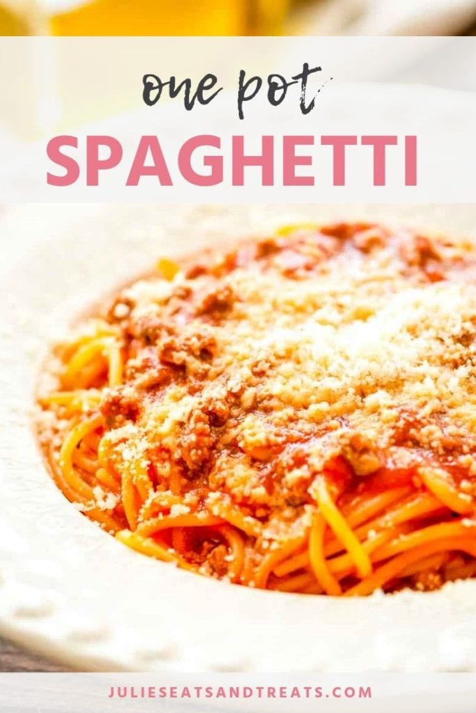 Spaghetti in a white bowl topped with parmesan