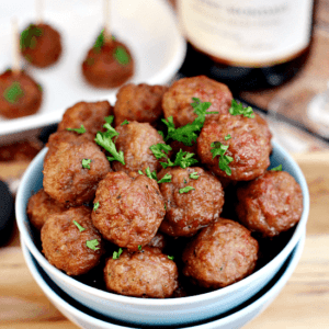 Two bowls stacked with the top full of cranberry pinot noir meatballs on a table in front of a white plate of meatballs with toothpicks in them and a bottle of wine