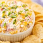 Corn Dip Recipe in white bowl on platter of tortilla chips