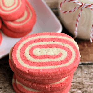 Stack of peppermint pinwheels on a table with a jar of milk and a plate of pinwheels