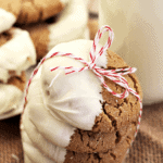 Stack of five white chocolate dipped gingersnaps tied together with red and white string on a burlap place mat with a glass of milk