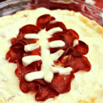 Football pepperoni pizza dip in a glass pie plate in front of a bowl of chips