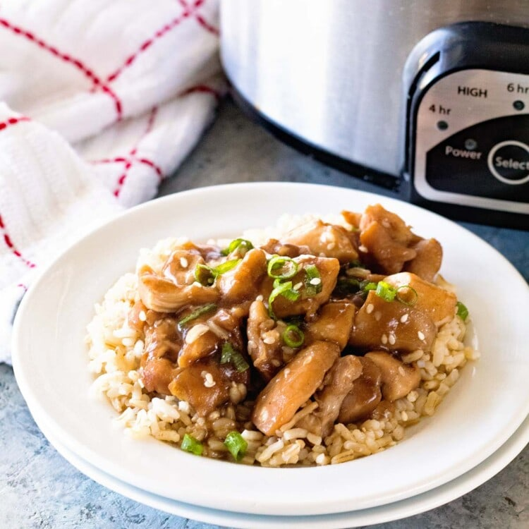 Slow Cooker Chicken Teriyaki over rice in a white bowl in front of a crock pot