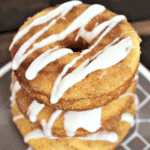 Three drizzled snickerdoodle donuts stacked on a brown and white plate