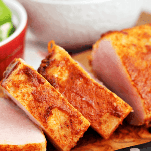 Slices of southwestern pork tenderloin on a cutting board with a knife
