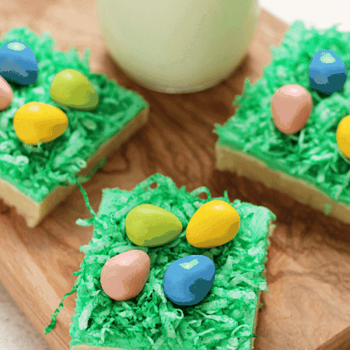 Three Easter egg hunt sugar cookie bars on a wood board with a glass of milk