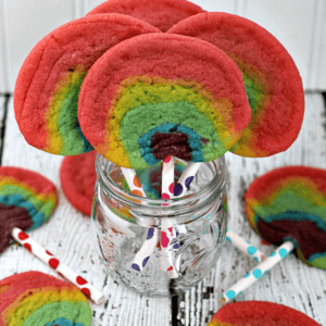 Four rainbow sugar cookie pops in a glass jar surrounded by five rainbow sugar cookie pops on the table