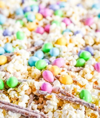 Snack mix spread out on wax paper with popcorn pretzels m&ms and peanuts with candy melts coating