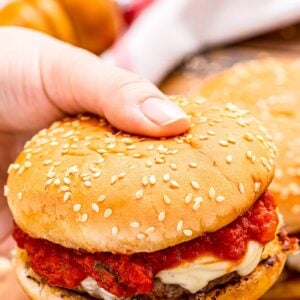 Hand holding burger with marinara sauce and mozzarella on it