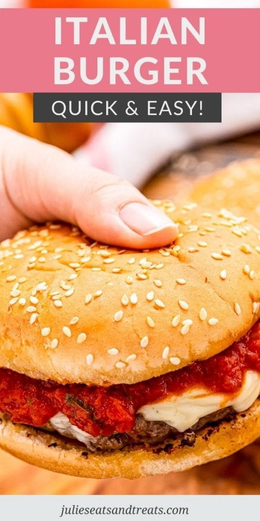 Hand holding an Italian burger topped with cheese and marinara sauce