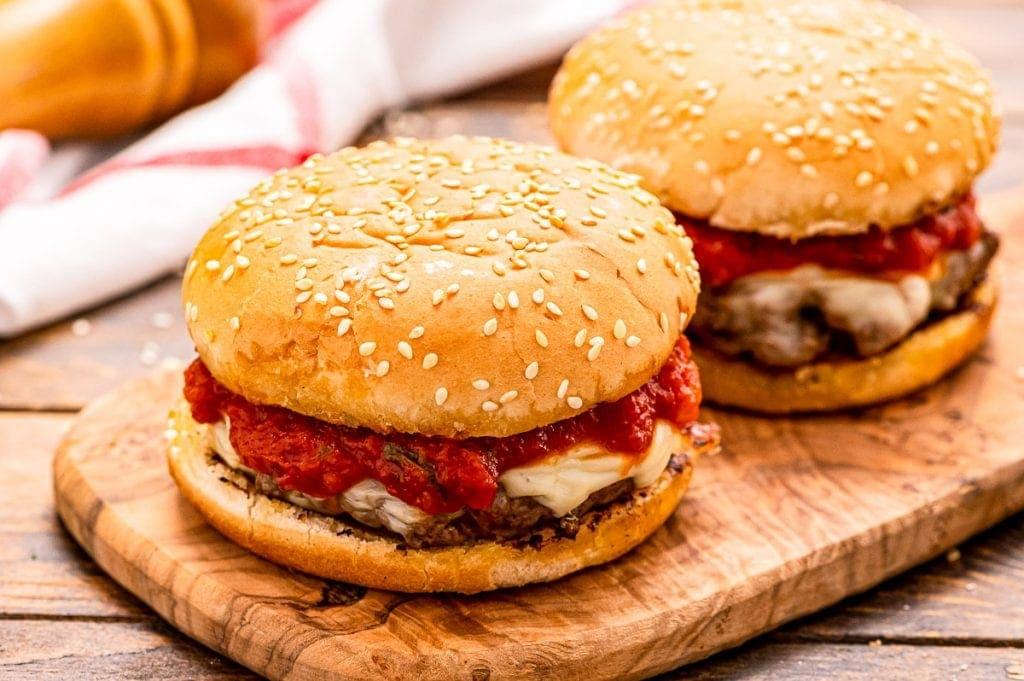 Italian Burger on a bun sitting on a wood cutting board