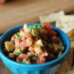Blue bowl of peach and tomato salsa on a table with tortilla chips