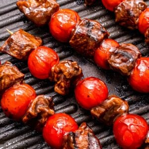 Grill pan with steak kebabs in it and grill marks on steak and cherry tomatoes