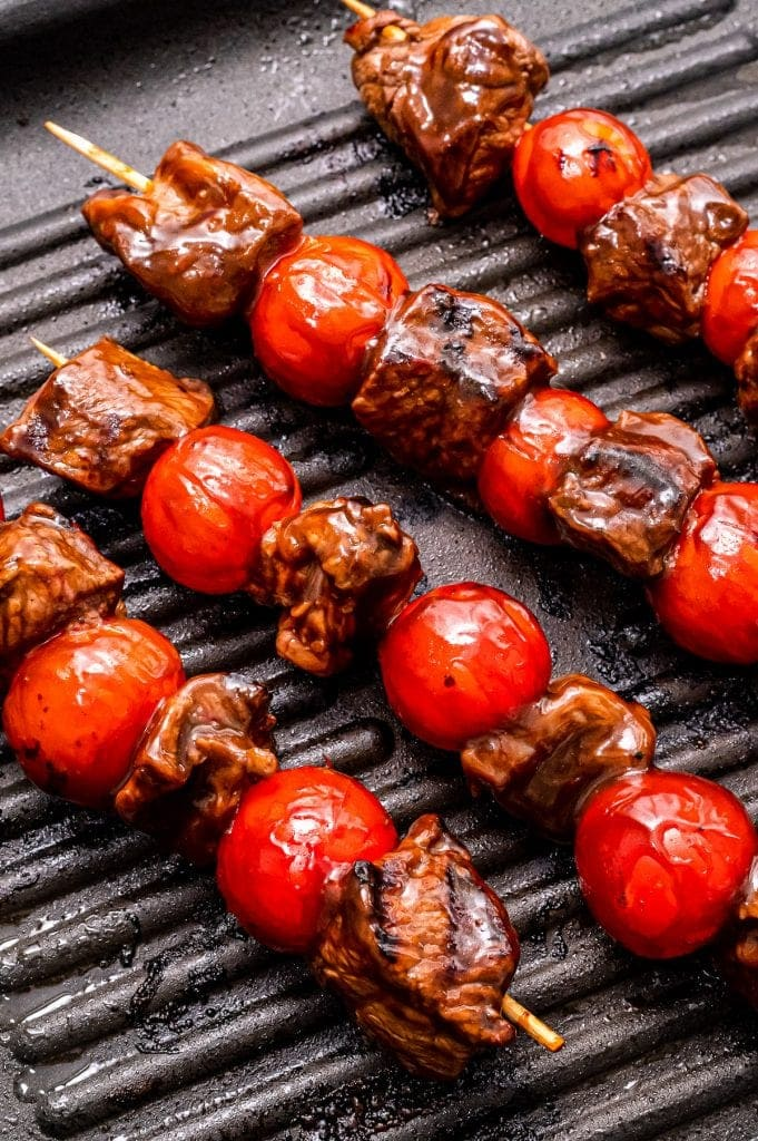 Grill pan with steak kabobs in it and grill marks on steak and cherry tomatoes
