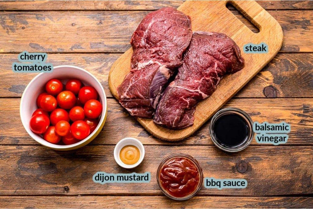 Ingredients for steak kabobs including cherry tomatoes steak dijon mustard balsamic vinegar bbq sauce