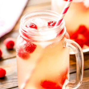 Moscato Lemonade in a mason jar with ice, raspberries, and a straw