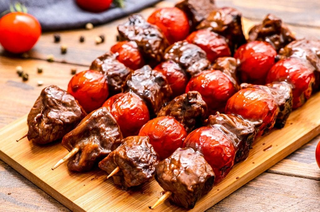 Wood cutting board with steak and cherry tomato kabobs on it
