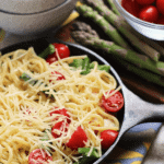 Small cast iron skillet of shrimp and asparagus pasta topped with shredded parmesan on a counter with asparagus and a bowl of cherry tomatoes