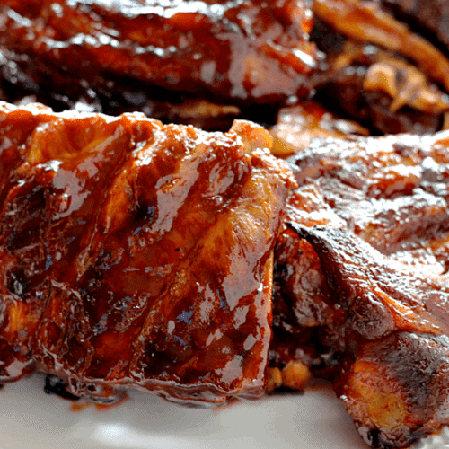 Several racks of smokey barbecue ribs on a white plate