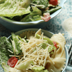 Two blue bowls of blt caesar pasta salad on a blue table cloth