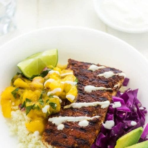 Fish taco bowl containing fish, avocado, limes, cabbage, and rice