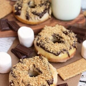 Three s'mores donuts on a table with marshmallows, chocolate bars, graham crackers and a glass of milk