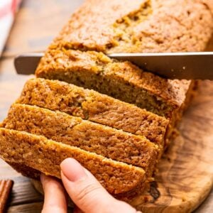 Hand holding a loaf of Banana Zucchini Bread while a knife slices it.