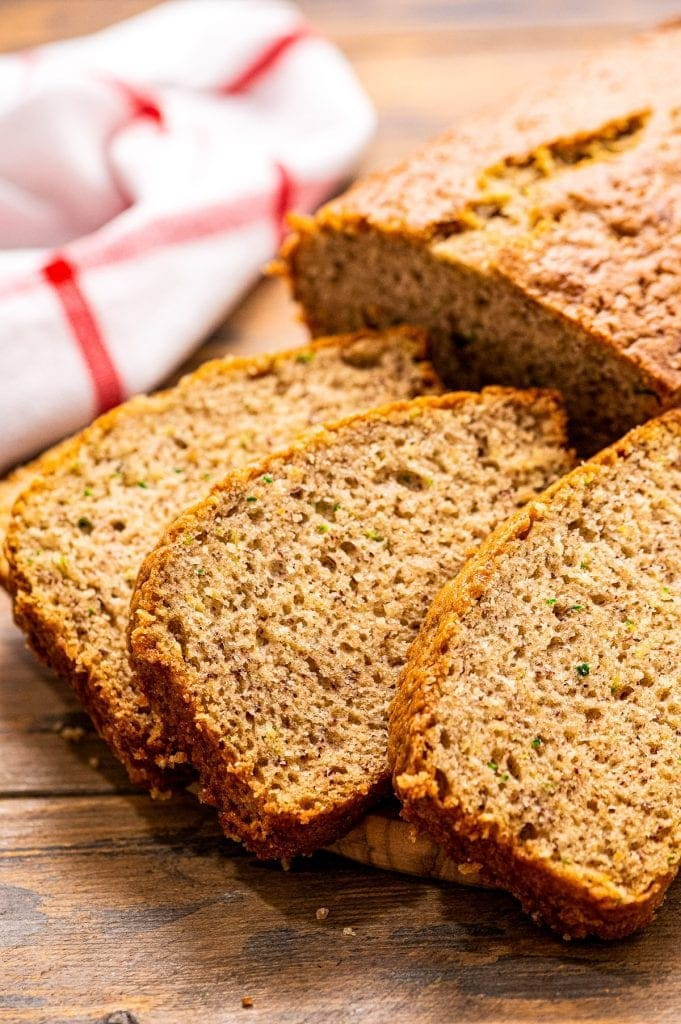 Three slices of Banana Zucchini Bread on wooden background with red and white striped napkin behind it.