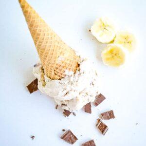 banana split ice cream cone upside down with chocolate chunks and banana slices
