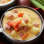 Two soup mugs of cheesy chowder next to celery sticks, carrots, and potatoes