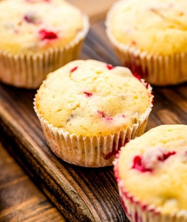 Cream Cheese Cranberry Muffins on wooden cutting board