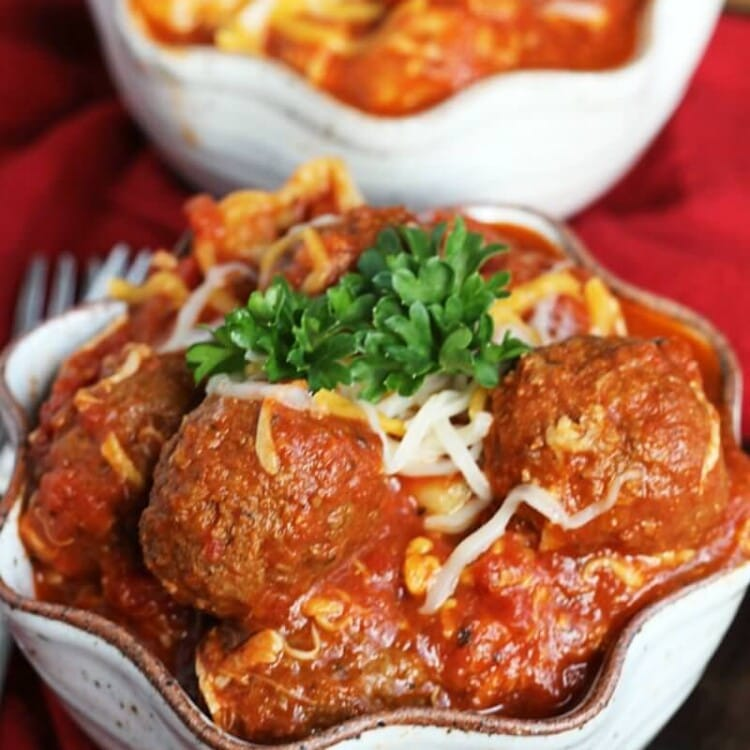 Two cream bowls of crock pot cheesy meatball tortellini on a red kitchen napkin