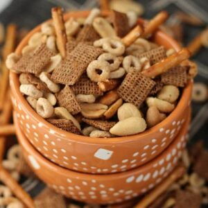 Two orange bowls stacked with the top full of crock pot chex mix and surrounded by chex mix on a napkin