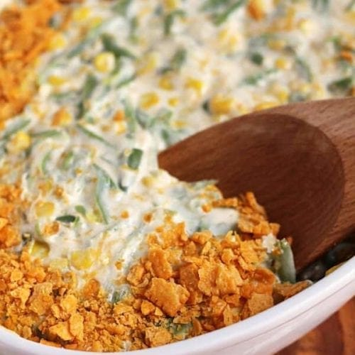 Green bean corn casserole in a white baking dish with a wooden spoon