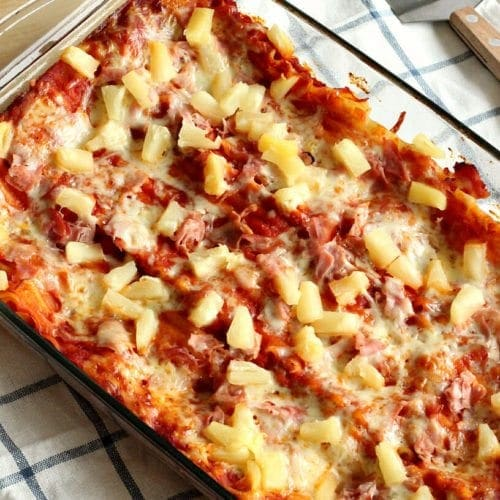 Hawaiian lasagna in a clear glass casserole pan sitting on a kitchen towel