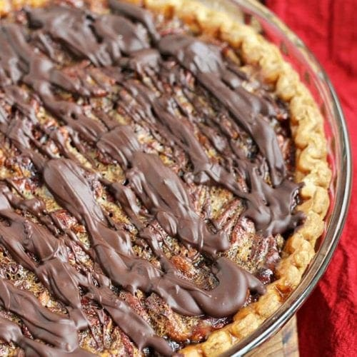 A clear glass pie plate containing a chocolate pecan pie