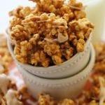Cinnamon bun popcorn in a white bowl spilling out onto an orange napkin