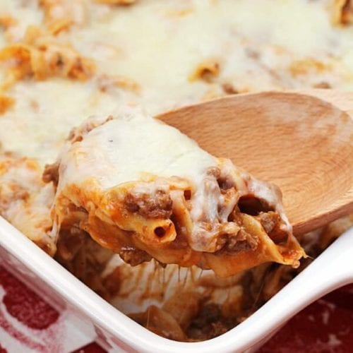 White baking dish of mom's pizza casserole with a wood spoon scooping pasta out