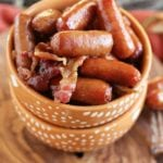 Two orange bowls stacked on a wood board with the top full of crock pot sweet bacon smokies