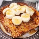 Two slices of crunchy pecan banana french toast topped with banana slices and syrup on a round plate