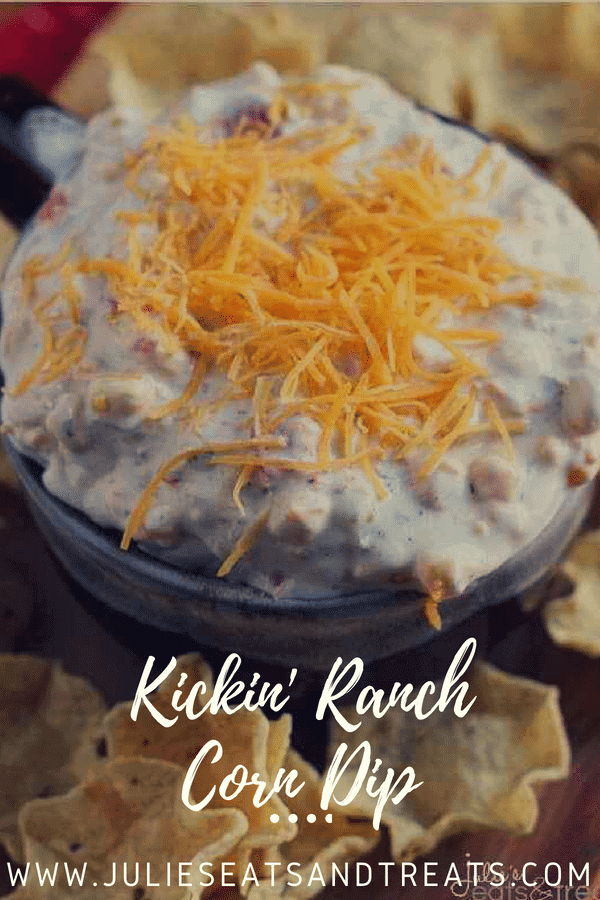 Kickin ranch corn dip in a bowl topped with shredded cheese and surrounded by tortilla chips