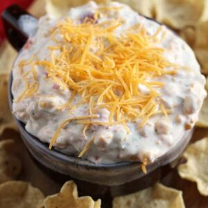Brown bowl of kickin' ranch corn dip topped with shredded cheese on a wood board with corn chips