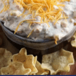 Kickin' ranch corn dip in a bowl topped with shredded cheese and surrounded by tortilla chips