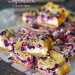 Berry cheesecake crumble bars stacked on wax paper