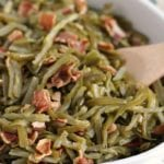 Crock pot bacon green beans in a white baking dish with a wooden spoon