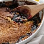A white oval baking dish full of lemon blueberry dump cake with a wooden spoon next to two lemons