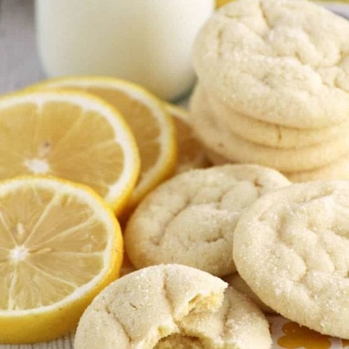 Lemon sugar cookies stacked on a yellow bag along with lemon slices and a glass of milk