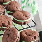 Mint chocolate sandwich cookies on a cooling rack over a mint green napkin next to a jar of green straws and a knife with green frosting on it